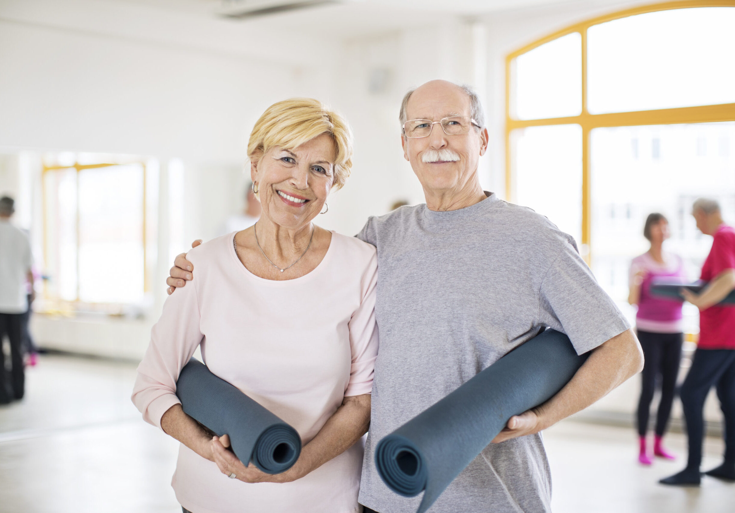 Portrait of happy senior couple holding rolled up exercise mats. Smiling man and woman are standing in yoga class. They are in sportswear.